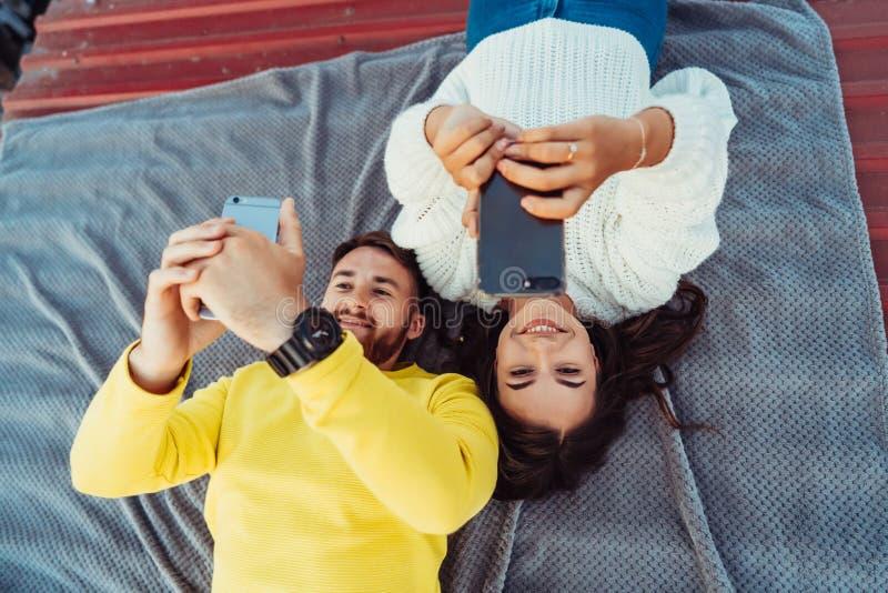 En stilig grabb och en ung flicka ligger på taket och rymmer smarfonsna fotografering för bildbyråer