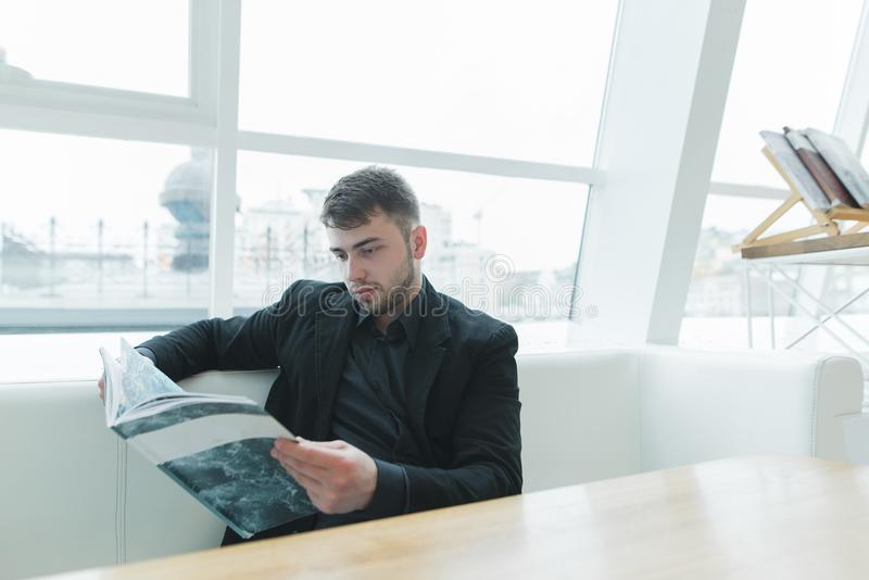 En stilig man i ett omslag och ett skägg läser en tidskrift i ett modernt ljust kafé Läs- avbrott royaltyfri bild