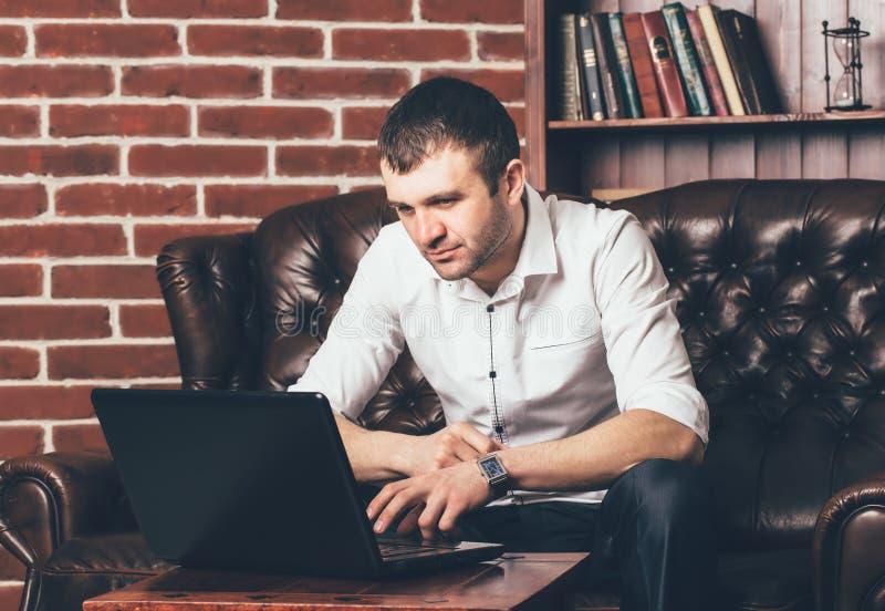 En stilig man läser information i bärbara datorn på bakgrunden av en hylla med böcker Affärsmannen sitter på en mjuk soffa i hans arkivfoto