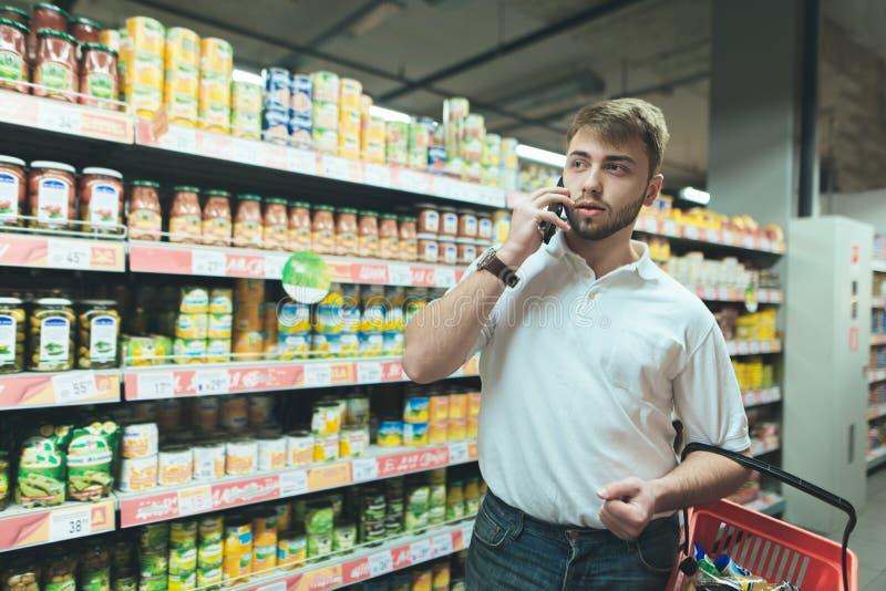 En stilig man med ett skägg talar vid telefonen på en supermarket Enkorg köpare väljer produkter arkivfoton