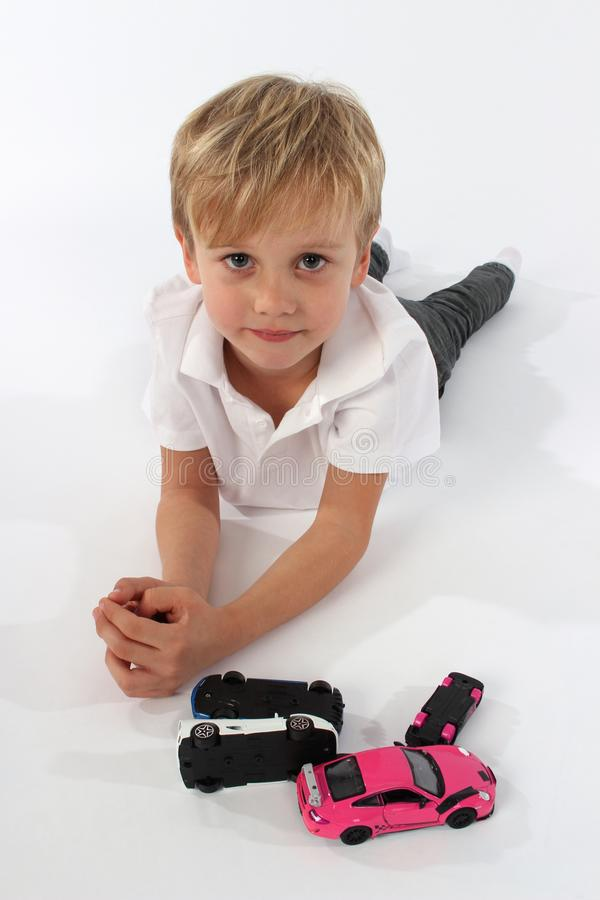 En stilig pojke för litet barn som ligger på golvet med en grupp av billeksaker arkivbilder