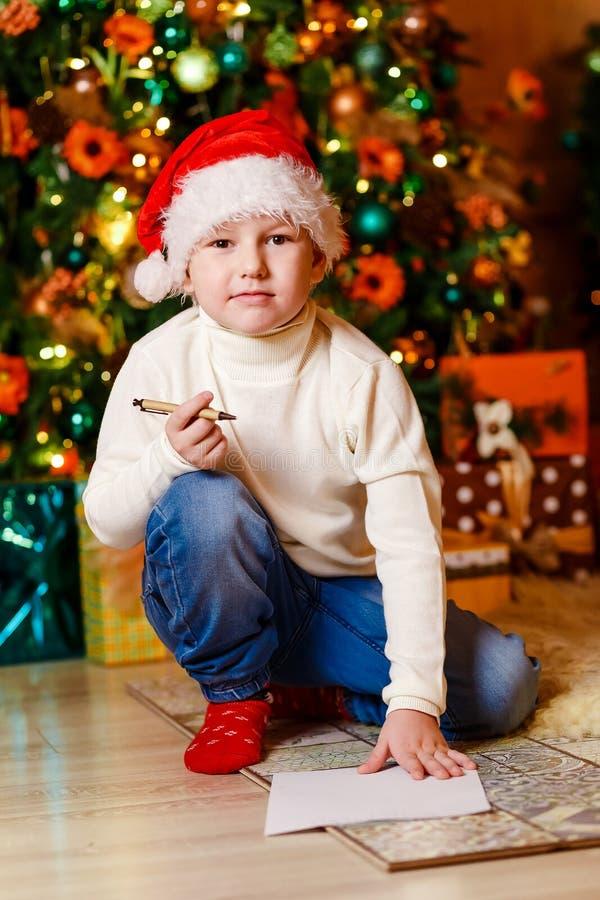 En stilig pojke i jultomten röda lock sitter under en julgran med ett stycke av papper och en penna royaltyfri foto