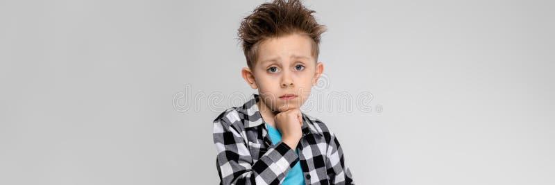 En stilig pojke i en plädskjorta, blå skjorta och jeans står på en grå bakgrund Pojken stöttar hans haka med hans royaltyfria bilder