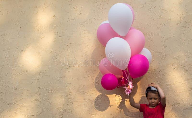 En stilig pojke rymmer i hans hand många kulöra ballonger arkivfoton
