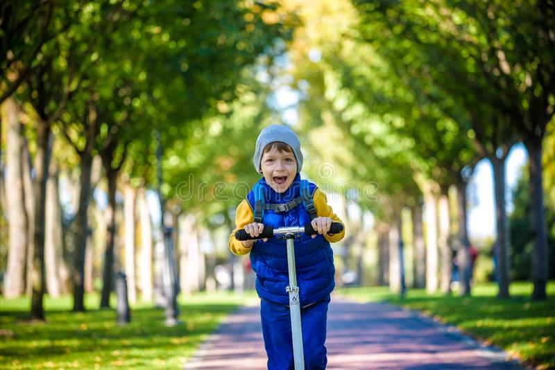 En stilig pojke som rider en sparkcykel i en höst, parkerar royaltyfria foton