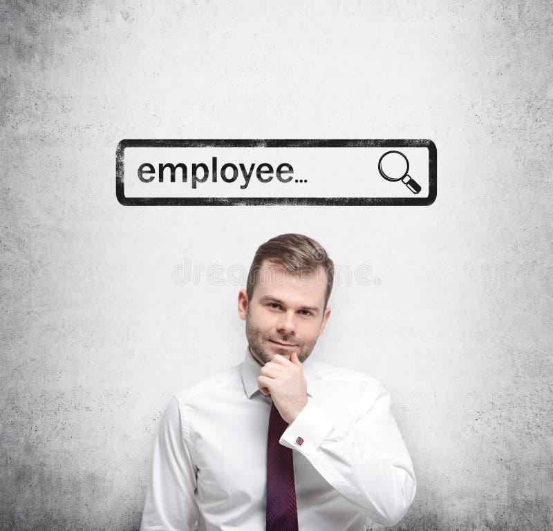 En stilig rekryterare, genom att rymma hans haka, söker efter nya anställda i internet Internetbegrepp av tillgängligt frankt för royaltyfri bild