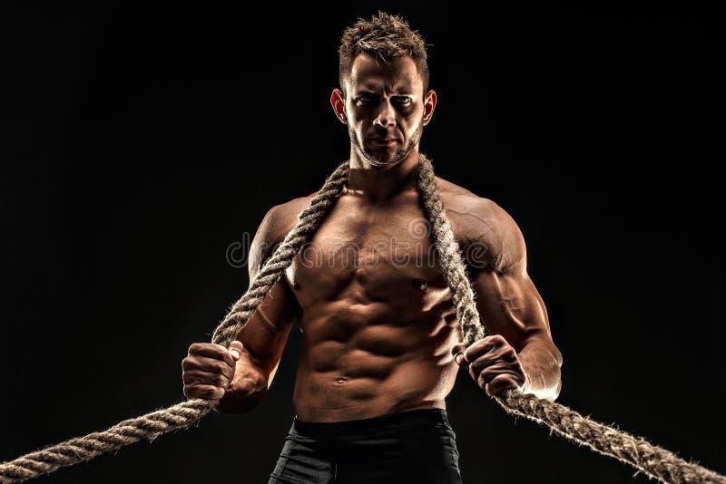 En stilig sexuell stark ung man med det hållande repet för muskulös kropp arkivfoto