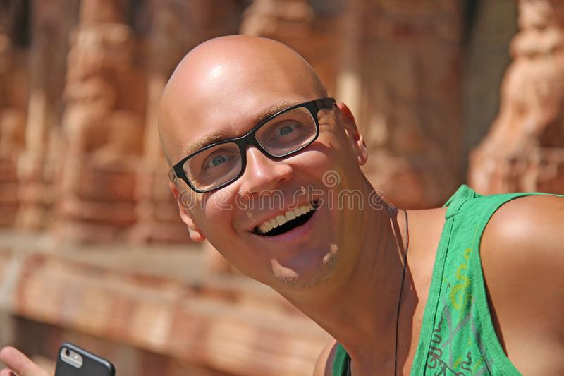 En stilig skallig man med exponeringsglas le för man inre tempel fotografering för bildbyråer