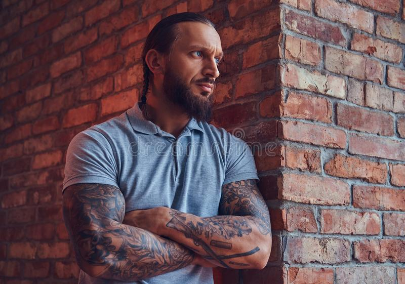 En stilig tattoed man med en stilfullt frisyr och skägg, i en grå t-skjorta, stående benägenhet mot en tegelstenvägg i a royaltyfri fotografi