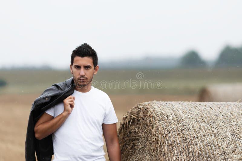 En stilig ung brunettman står i ett fält nära en höstack royaltyfria foton
