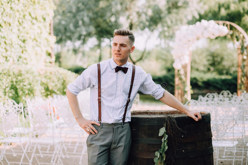 En stilig ung manlig brudgum i en skjorta, en fluga, en byxa och en hängslen poserar bredvid en trumma för vin royaltyfria foton
