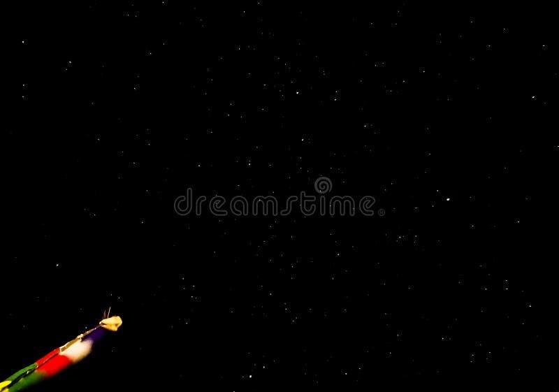 En stjärnklar natt med en färgad flagga fotografering för bildbyråer