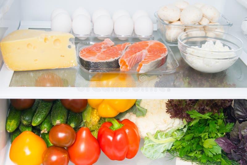 En stock blanc de nourriture de réfrigérateur, sur les oeufs d'étagère supérieure, les poissons, champignons, fromage blanc, vian images libres de droits