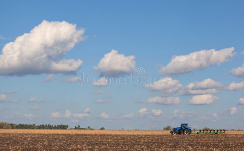 En stor blå traktor som plogar fältet mot den härliga himlen fotografering för bildbyråer