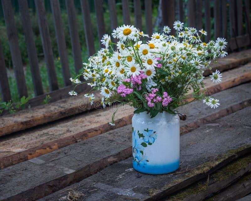En stor bukett av lösa blommor av tusenskönor och nejlikor i på burk med en modell som utomhus står på gamla bräden arkivbilder