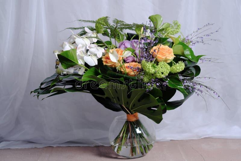 En stor bukett av olika blommor, rosor, callanejlikor, står i en exponeringsglasvas på golvet royaltyfri foto