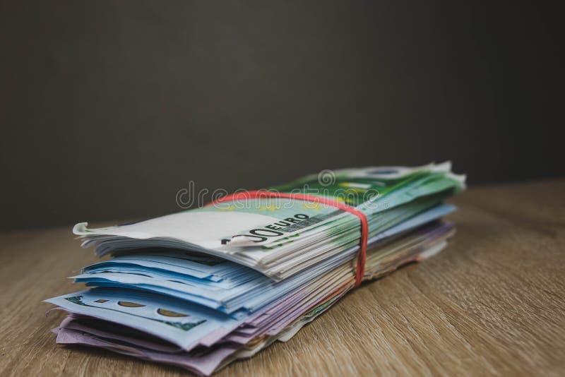 en stor bunt av rubel för euro för kassaräkningdollar i packar på en tabell av texturerade bräden royaltyfri bild