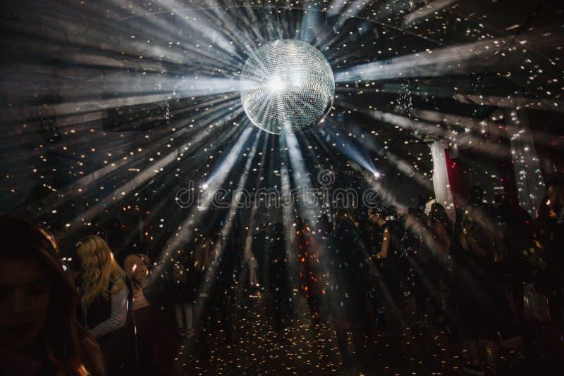En stor diskoboll hänger från taket Mycket folk dansar på bakgrunden royaltyfri fotografi