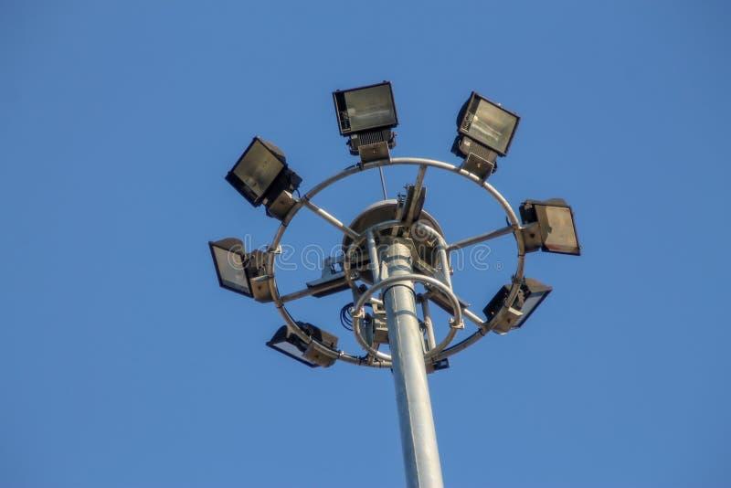 En stor elektrisk pol som fylls med str?lkastare i den bl?a himlen royaltyfria foton