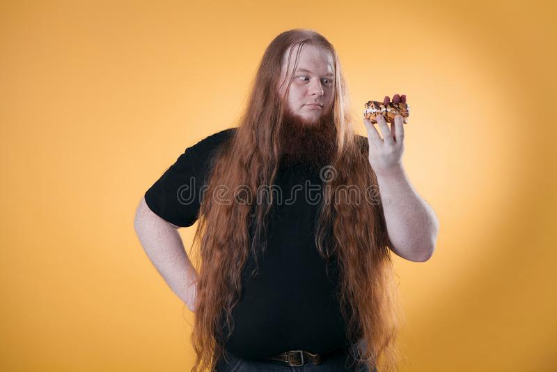 En stor fet man rymmer en söt kaka i hans hand royaltyfri foto