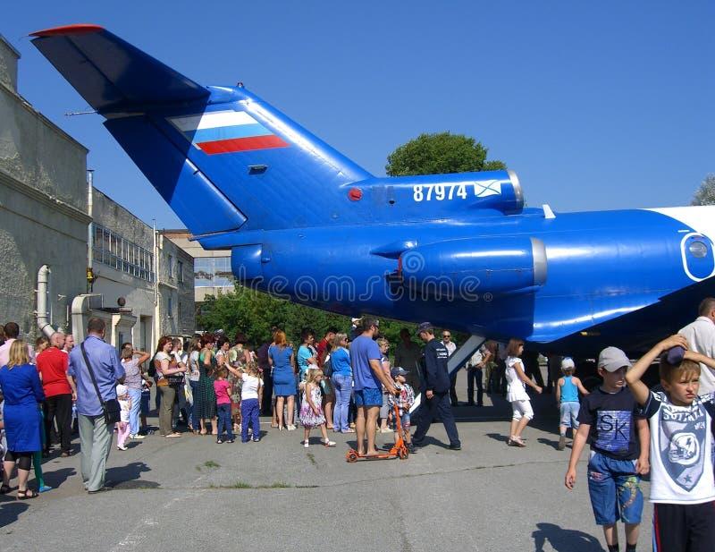 En stor folkmassa av barn för folkkvinnamän på ferieblick på svansen av flygplanet går royaltyfri foto