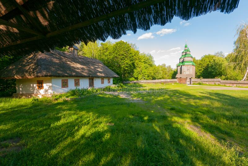 En stor gammal ukrainarekoja på bakgrunden av en träkyrka i avståndet royaltyfri bild