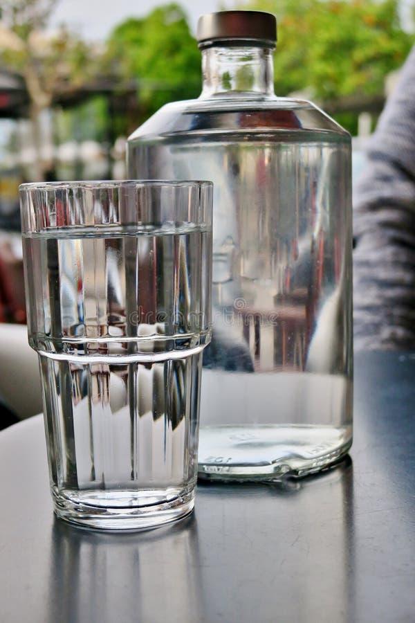 En stor genomskinlig flaska av vatten med ett n?sta exponeringsglas, n?rbild royaltyfria foton
