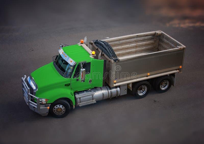 En stor grön Caterpillar lastbil som är klar för en påfyllning av spillror royaltyfria foton