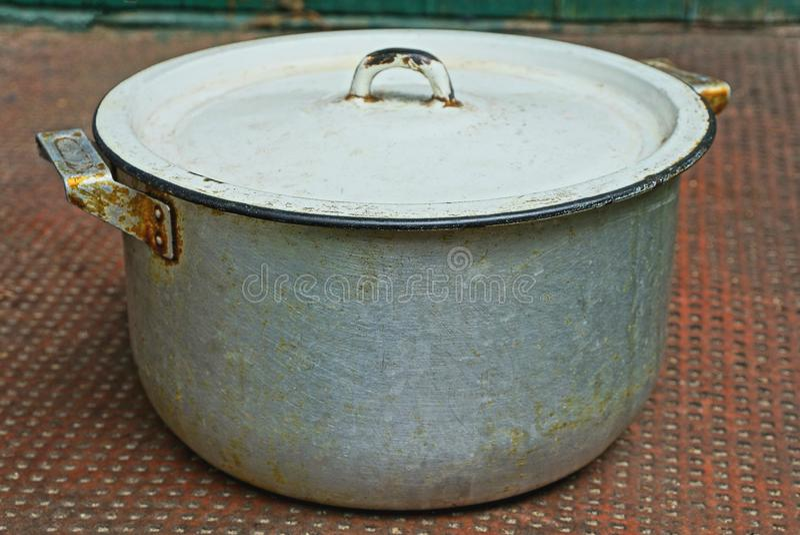 En stor gr? smutsig aluminiumpanna som t?ckas med ett vitt lock fotografering för bildbyråer