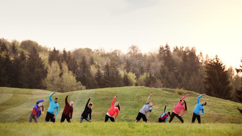 En stor grupp av mång- utvecklingssportfolk som står i natur som sträcker arkivfoton