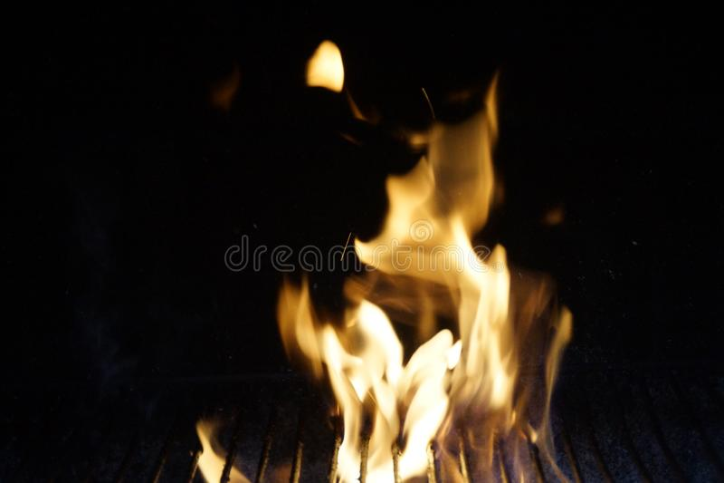En stor gul flamma i en grillfest arkivfoto