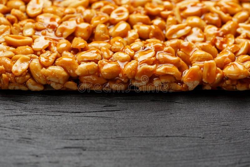 En stor guld- tegelplatta av jordnötter, en stång i söt melass på en svart texturbakgrund Kozinaki användbara och smakliga sötsak arkivbilder