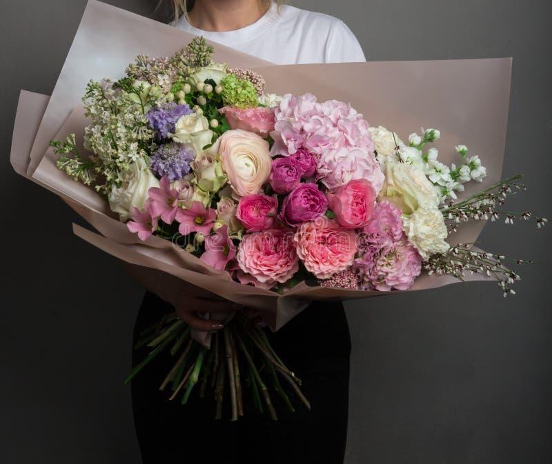 En stor härlig fördelande bukett av blommor i händerna av en flicka, arbetet av en blomsterhandlare royaltyfri bild
