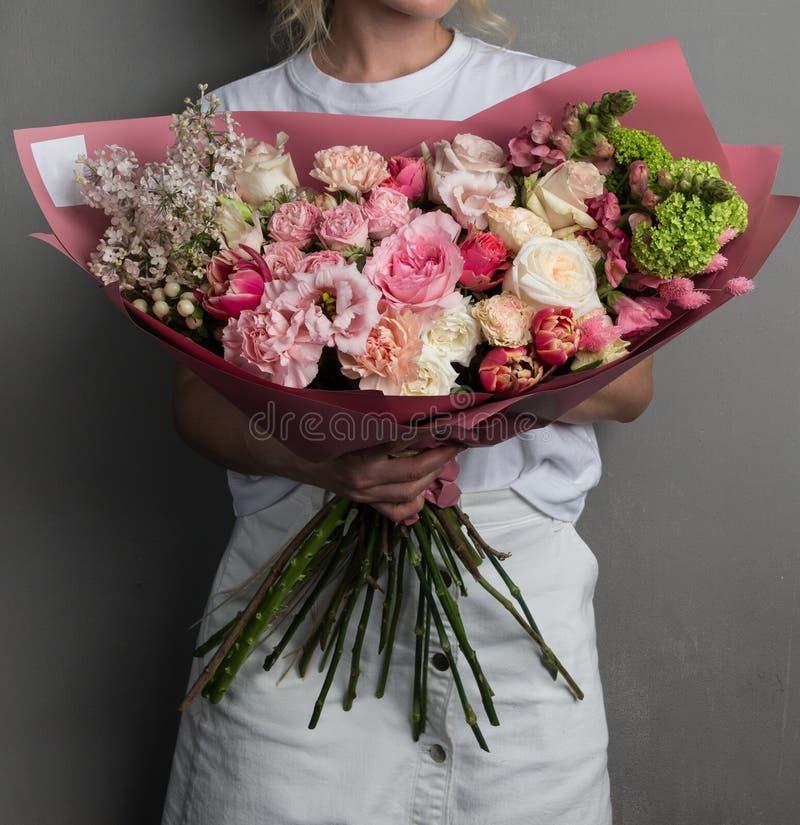 En stor härlig fördelande bukett av blommor i händerna av en flicka, arbetet av en blomsterhandlare arkivfoto