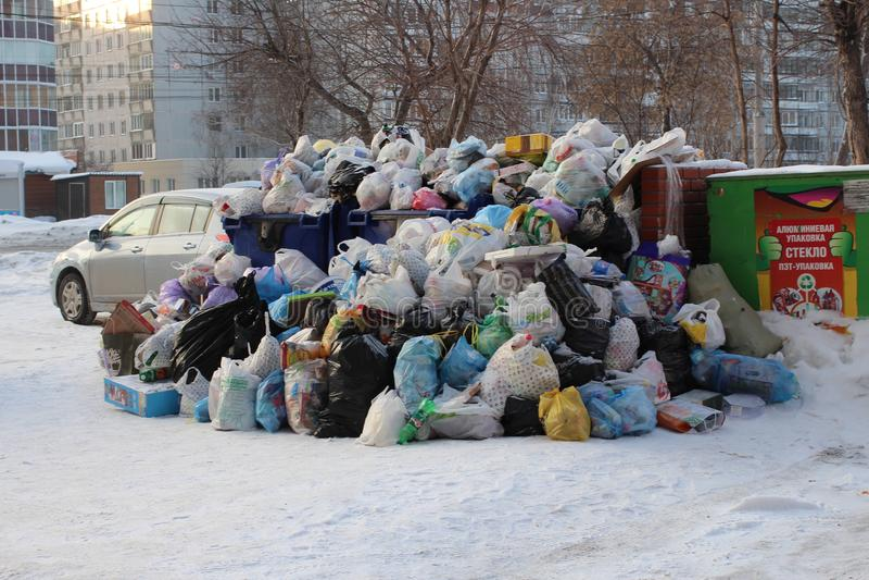 En stor hög av plastpåsar av avskräde- och hushållavfalls i stadsförrådsplatsen i vintern i Novosibirsk förorenar miljön arkivfoto