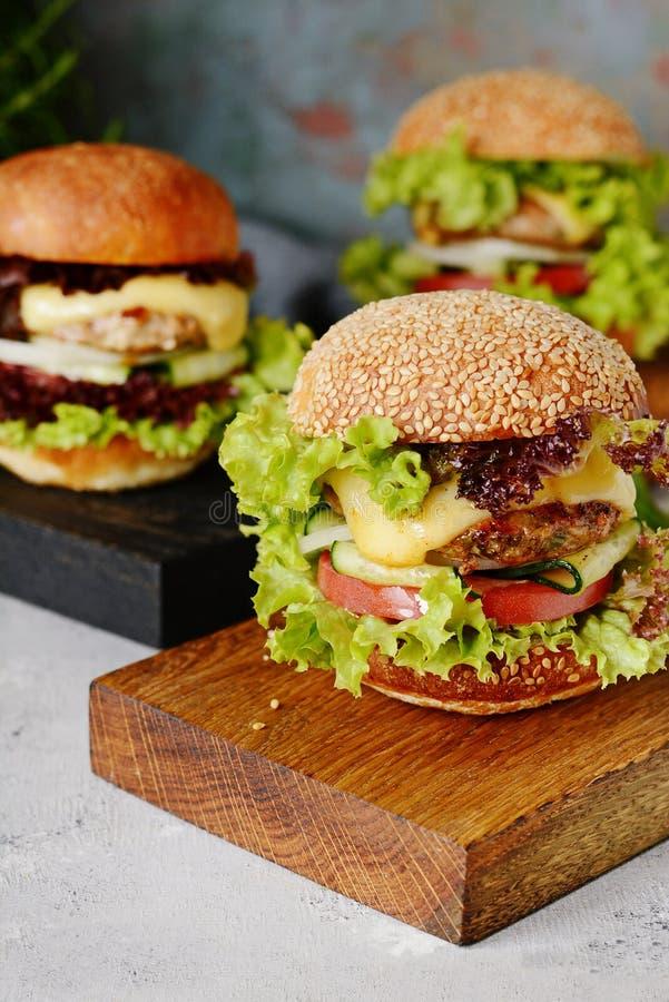 En stor hamburgare med en kotlett, grönsaker och en ny rulle Smörgås för frukostsnabbmat Tjäna som ett mellanmål på ett träbräde arkivfoto