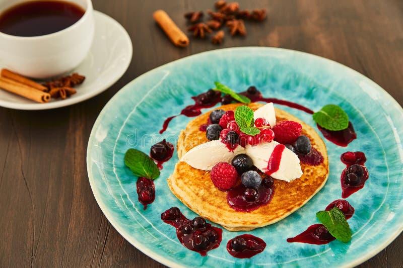 En stor hemlagad pannkaka med vit mascarponekräm, hallon, blåbär, vinbär, bär och honung på en blå platta Det är royaltyfri foto
