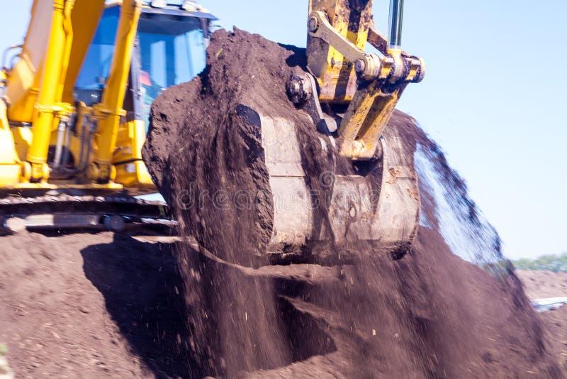 En stor järngrävskopahink samlar och häller sandspillror och stenar i ett villebråd på konstruktionsplatsen av väglättheter royaltyfri fotografi