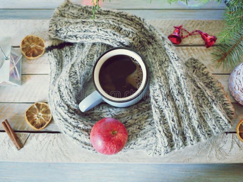 En stor kopp kaffe, ett äpple, en stucken woolen halsduk på en trätabell med juldekoren, brinnande stearinljus, granfilialer royaltyfri foto