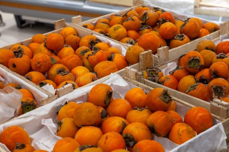 En stor kugge med träkorgar med persimoner i fruktavdelningen av köpcentret Nya och sunda foods för varje royaltyfria bilder