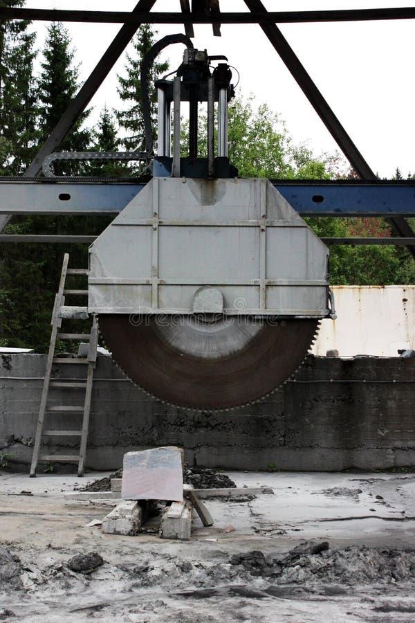 En stor maskin med en cirkelsåg för att klippa enorma marmormellanrum och stenar för framställning av tjock skiva bredvid kanjone royaltyfri bild