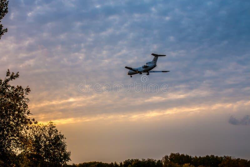En stor passagerarenivå går på landning på solnedgången skjuta i parkera mot bakgrunden av höstträd royaltyfri bild