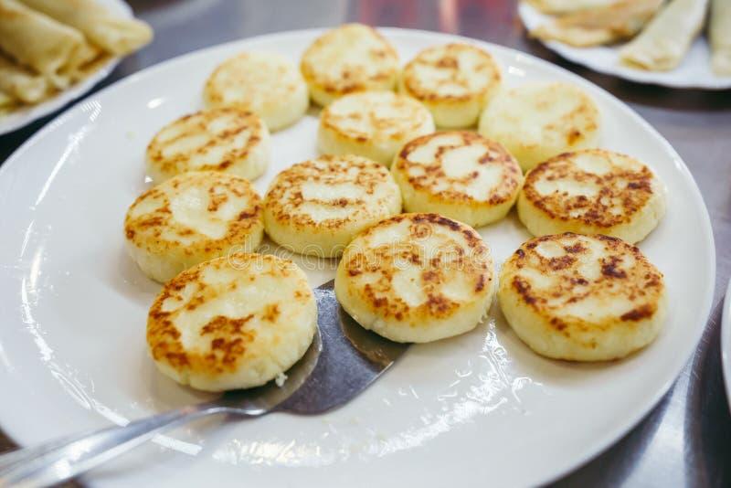 En stor platta med ostmassaost för frukosten, kesopannkakor, ostmassastruvor med nya bärjordgubbar royaltyfria bilder