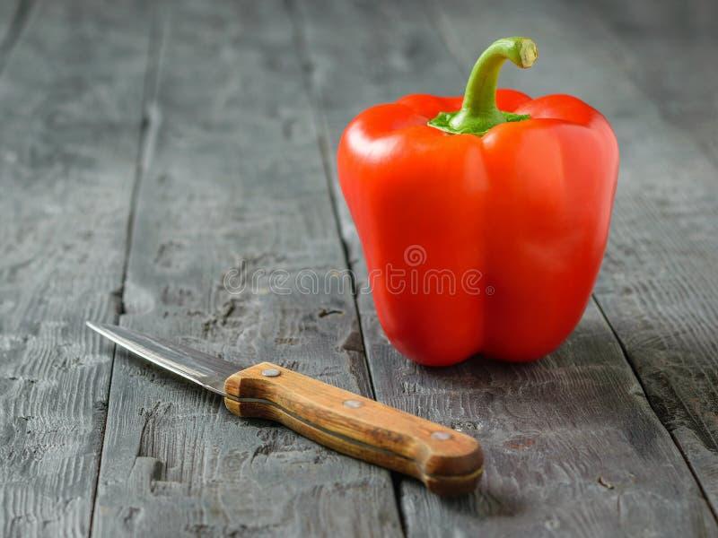 En stor röd spansk peppar med en kniv på en svart lantlig tabell Vegetarisk mat arkivbilder