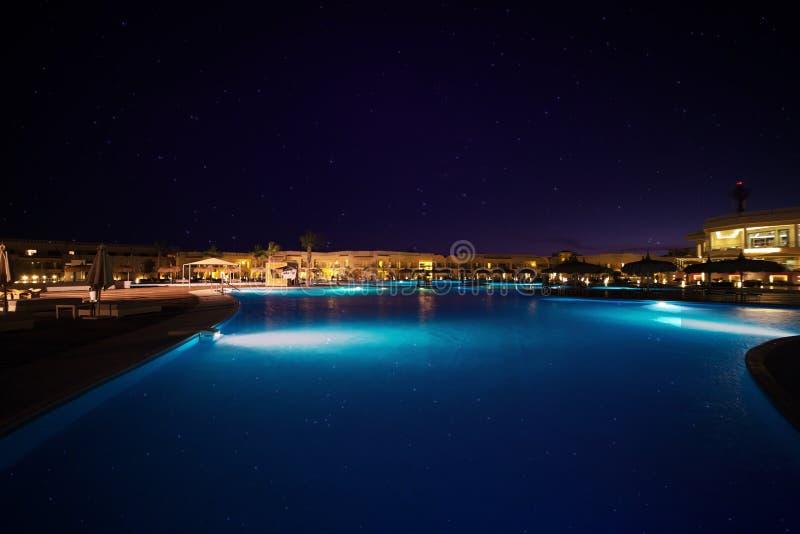 En stor simbassäng på natten under stjärnor royaltyfri bild