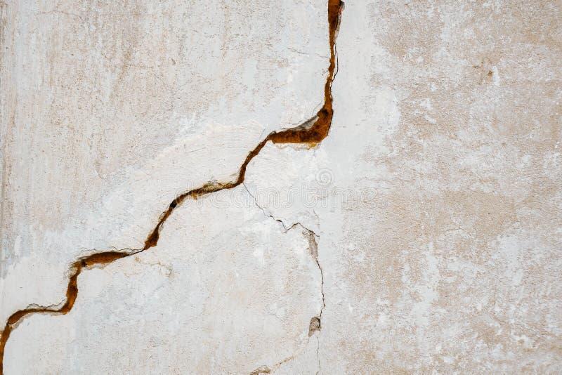 En stor spricka p? den gr?a v?ggen abstrakt bild som projekterar en spricka i en vit betongv?gg royaltyfria foton