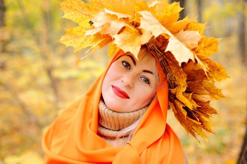 En stor stående av en härlig medelålders blondin i en krans av höstsidor, som står i en orange halsduk i royaltyfri fotografi