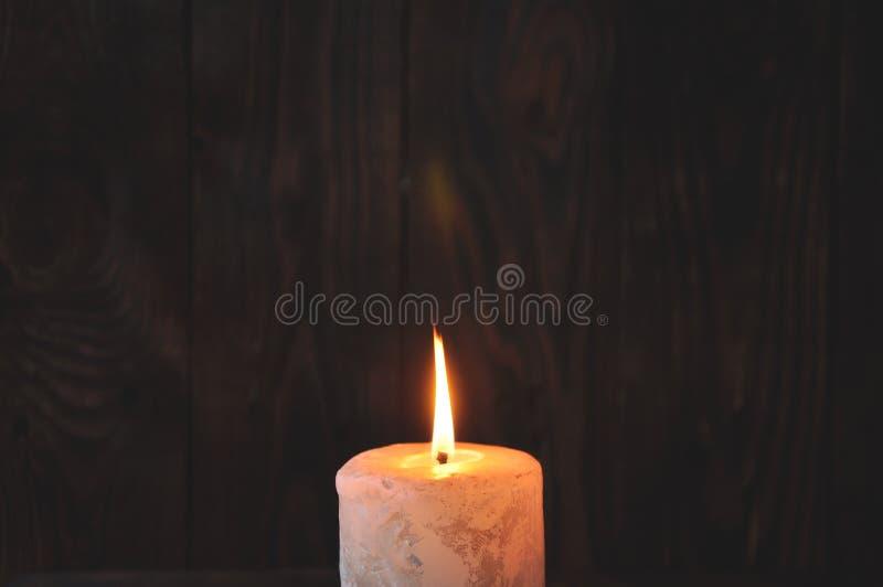 En stor stearinljus bränner i mörkret på en trätexturbakgrund arkivbild