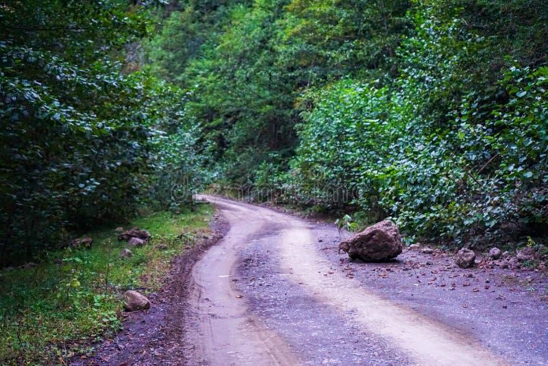 En stor sten avverkar på en smutsbergväg efter regnet arkivfoton