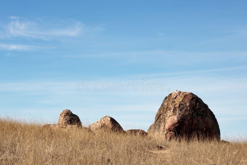 En stor stenblock och tre mindre stort vaggar uppsättningen mot blå himmel med vita wispy moln, torrt gräs i förgrund arkivfoto